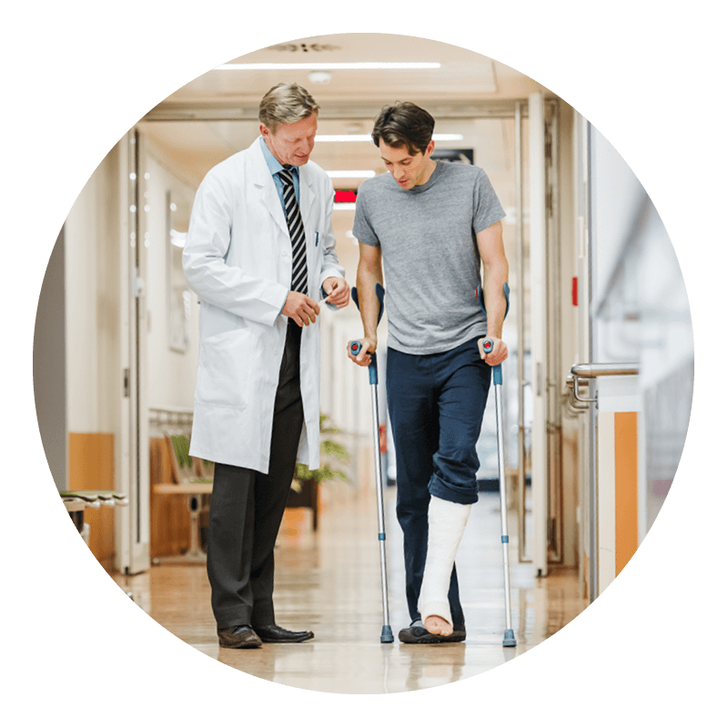 A doctor walking with a patient in a cast
